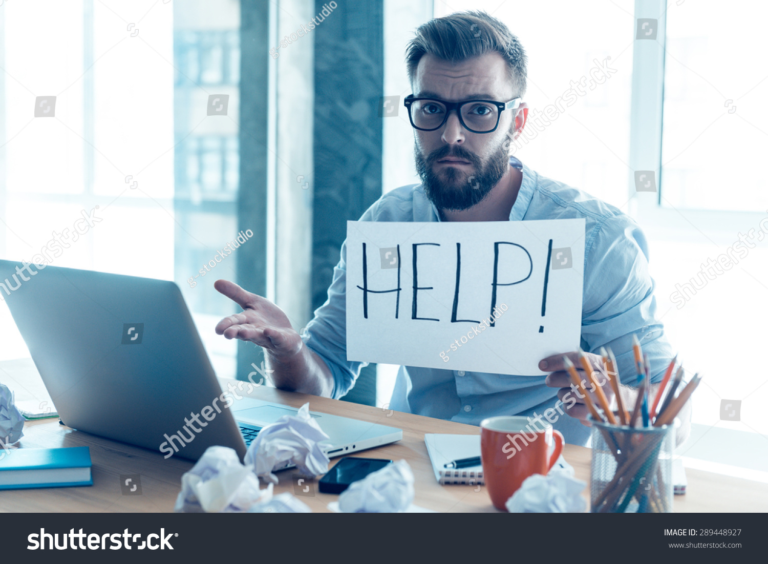Frustrated office worker on the phone holding stock photo image - Frustrated Young Beard Man Holding Piece Of Paper And Asking For Help