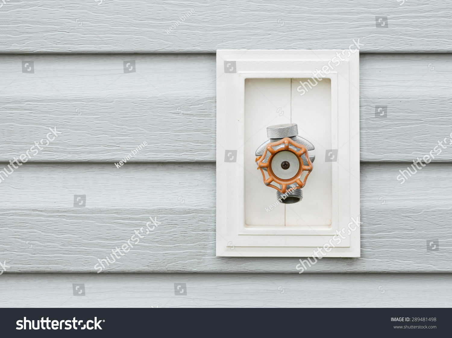 Outdoor Water Faucet On Exterior House Siding Stock Photo