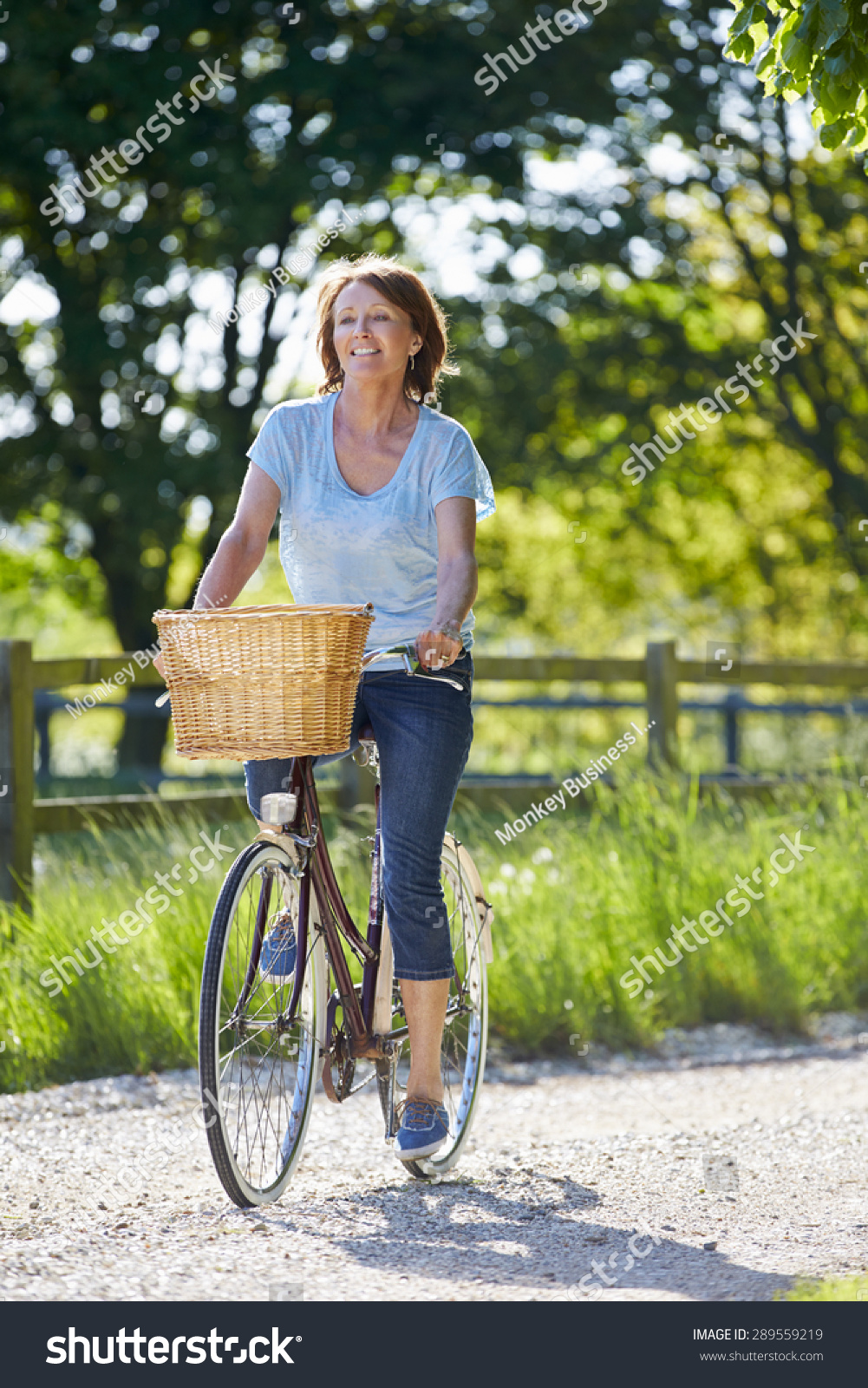 attractive mature woman riding bike along stock photo (royalty free