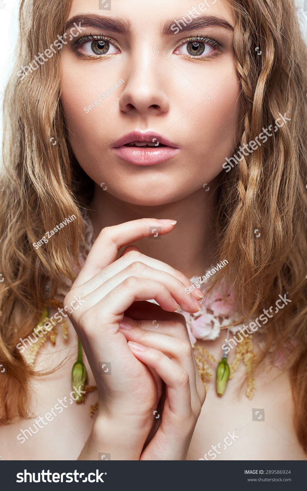 Close-up portrait of teen girl with flower necklace and hand near face