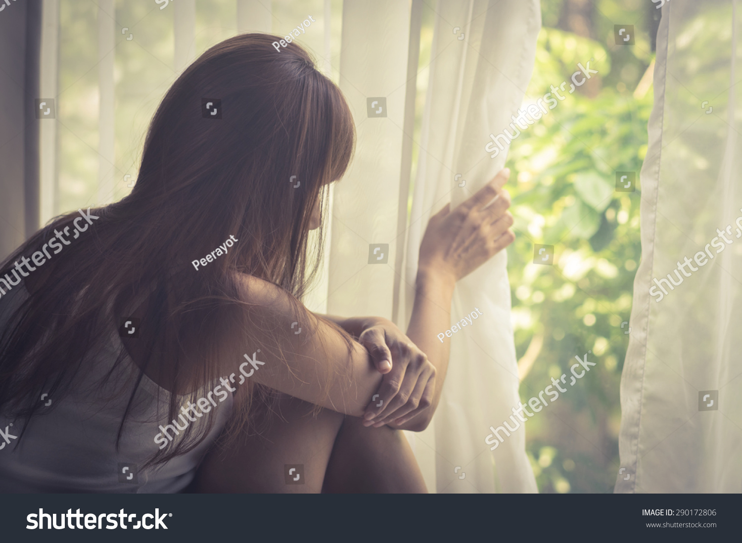 Sad girl looking out of window vintage filtered