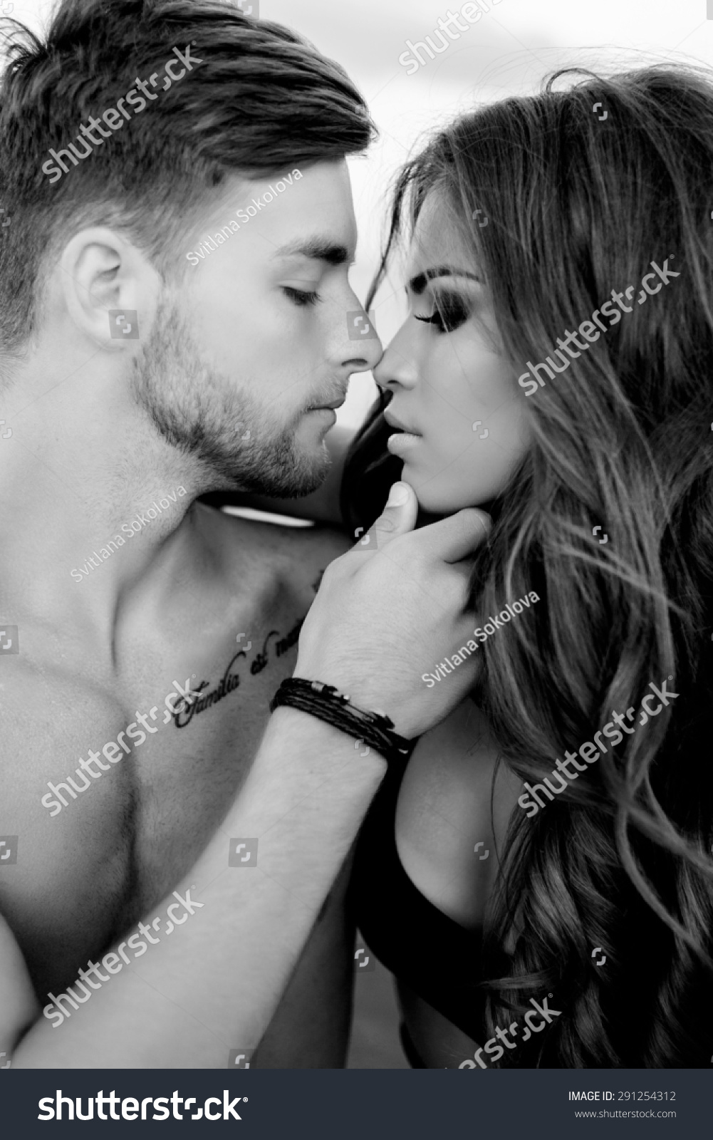 Close up portrait of romantic couple in love kissing sexy woman and handsome man posing on the beach black and white image