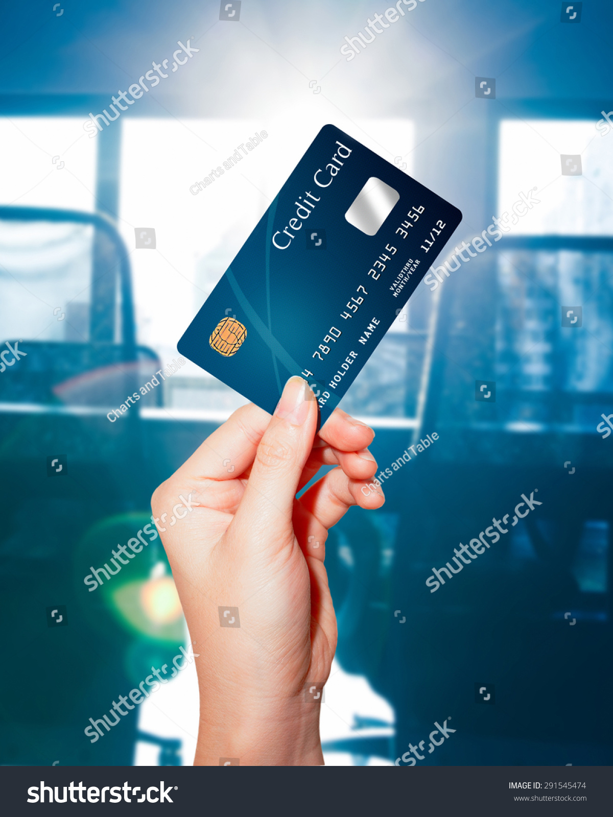 female hand holding credit card against stock photo