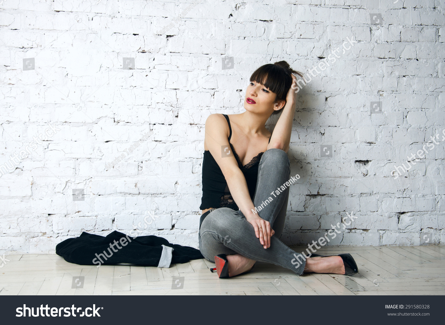 ee59a65a1ce Pretty sexy woman model with amazing body long legs seating on the floor  wearing denim jeans