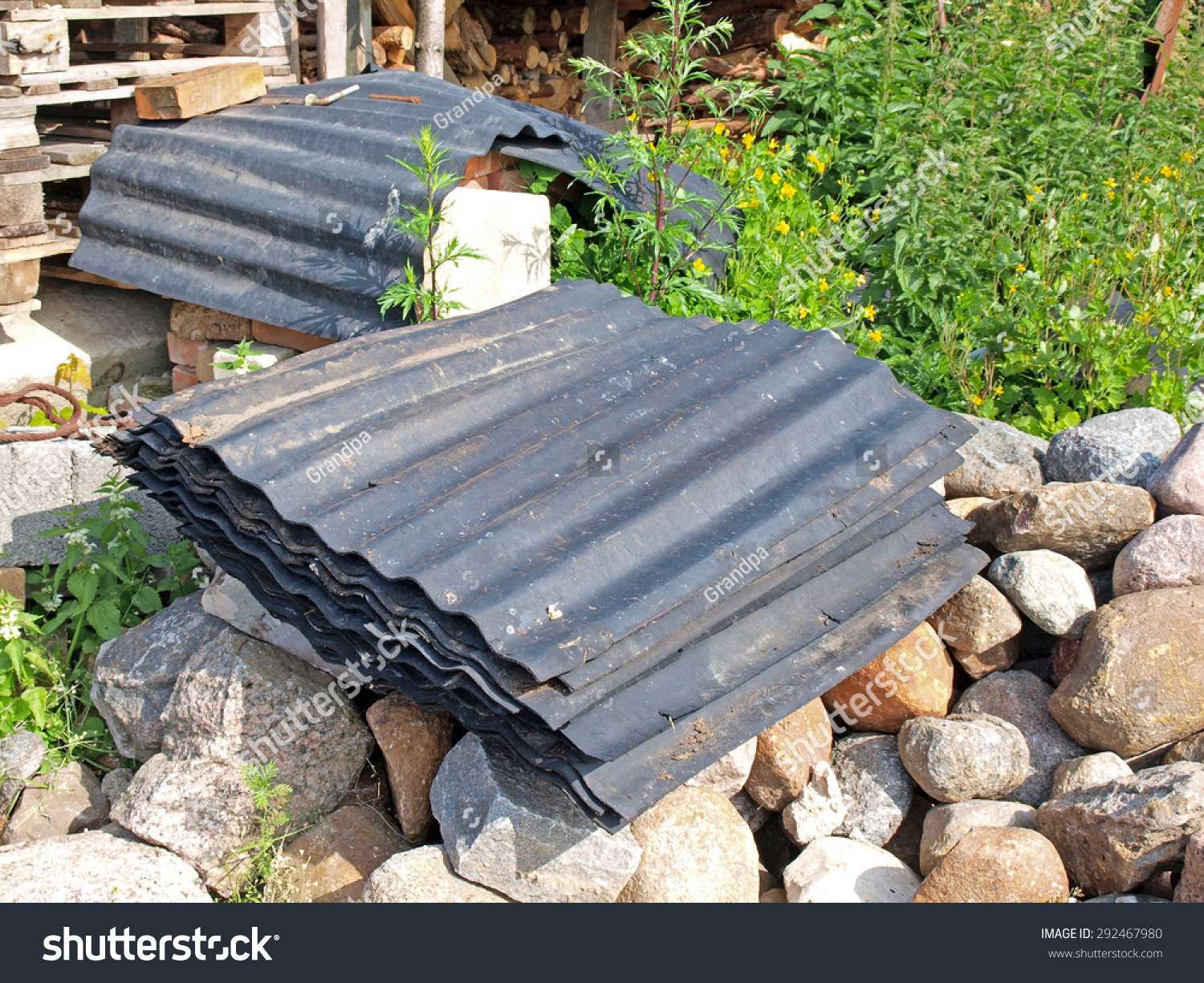 Old Used Black Rubber Roof Tiles Waved Made From Recycled Tires Outdoor  Stacked On Stones.