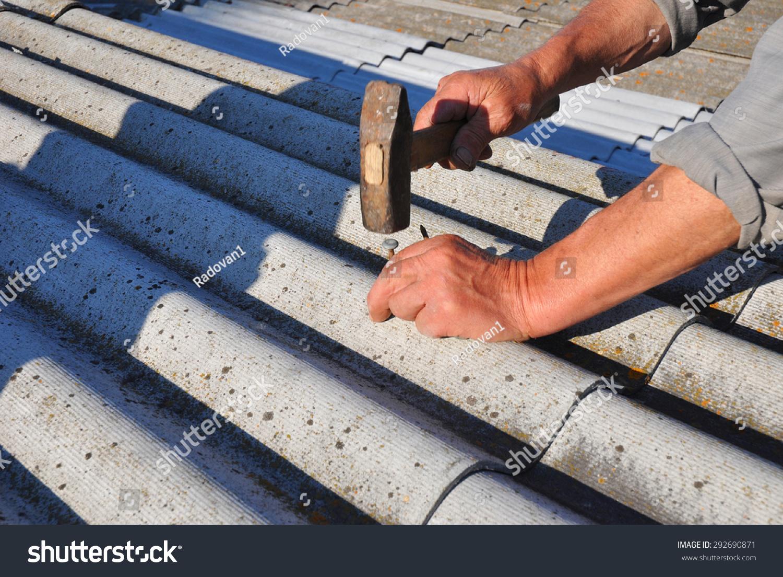 Repair Dangerous Asbestos Old Roof Tiles. Worker Installs Asbestos Roof  Shingles   Closeup On Hands