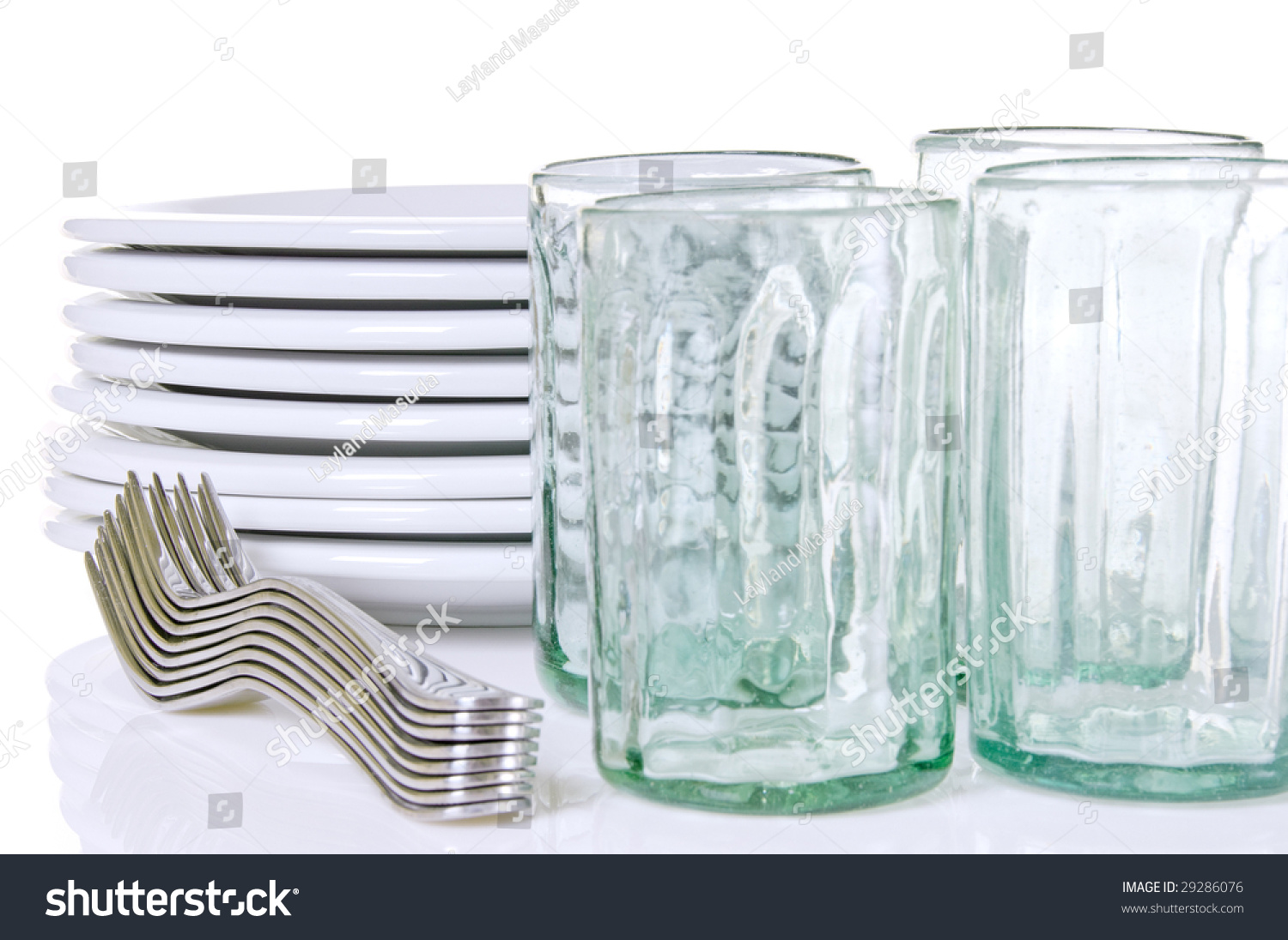 stack of dinner plates forks and several hand blown drinking glasses with focus on