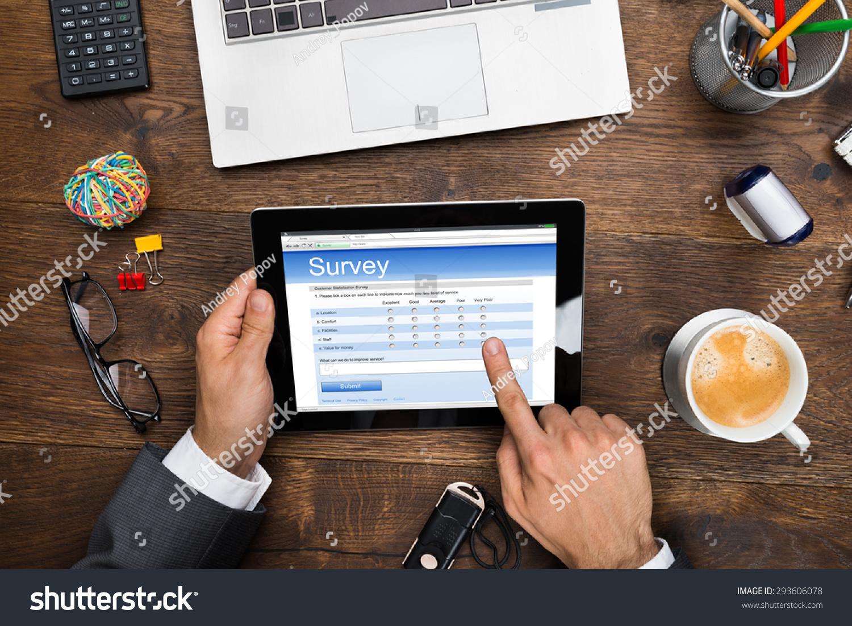 close up of a businessman filling online survey form on digital tablet stockfoto 293606078. Black Bedroom Furniture Sets. Home Design Ideas