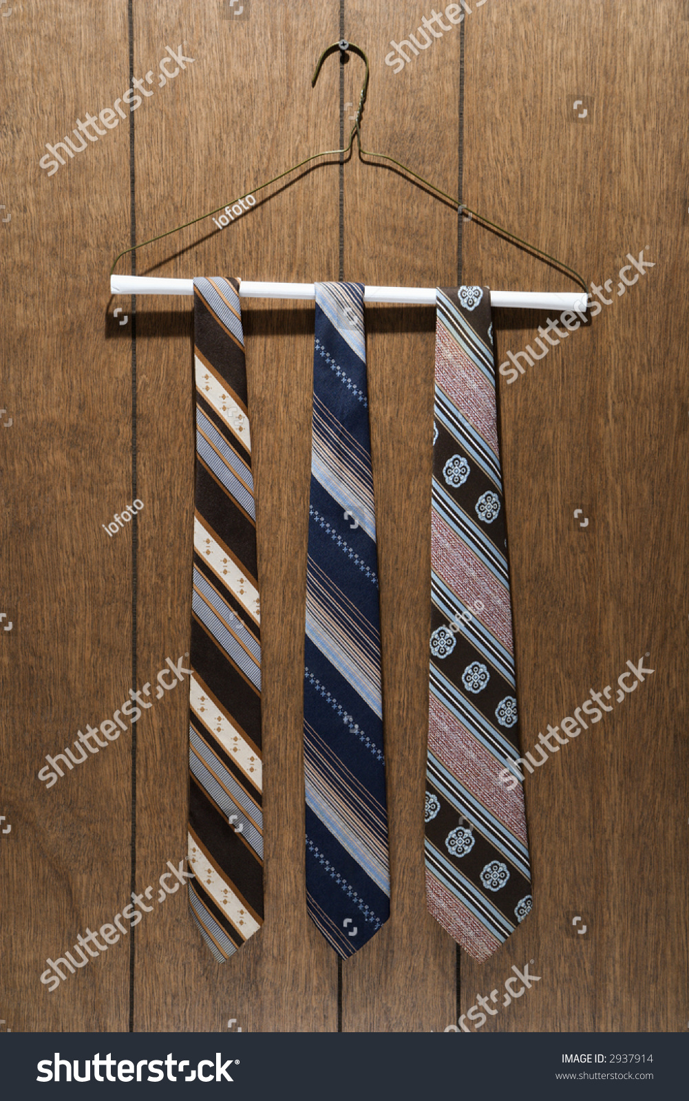 Three Retro Ties Hanging On A Wire Hanger Against Wood