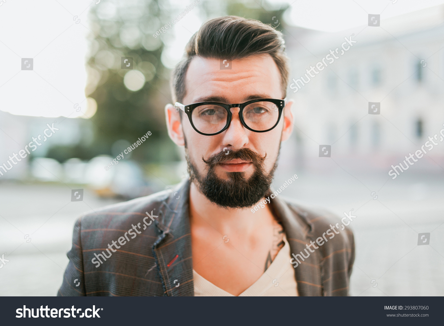 young guy with a beard and mustache with glasses in a suit posing on the street in the sunlight fashion man style vintage style retro men handsome beard outdoor portrait close up