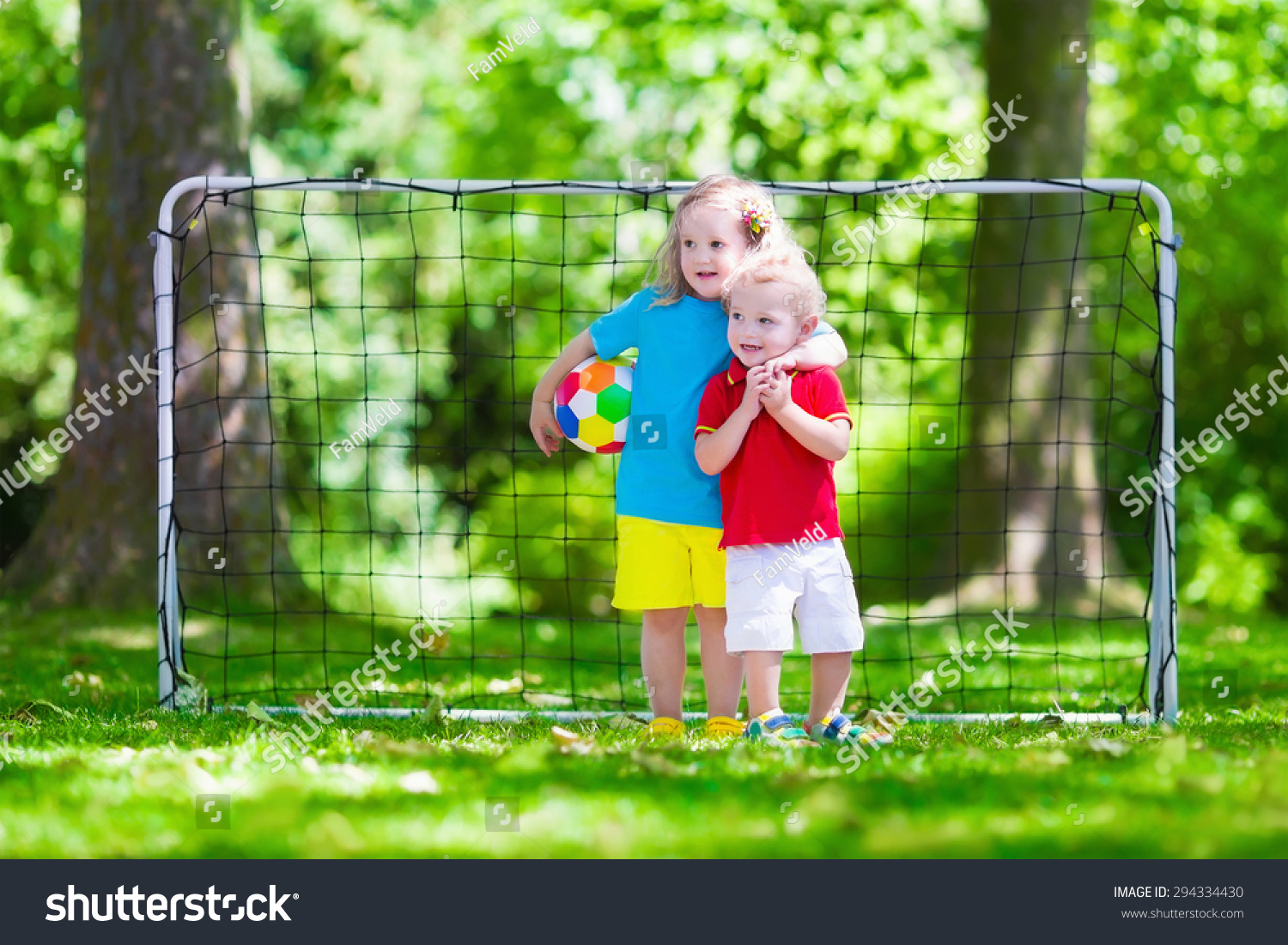 Two happy children playing european football stock photo for Childrens play yard