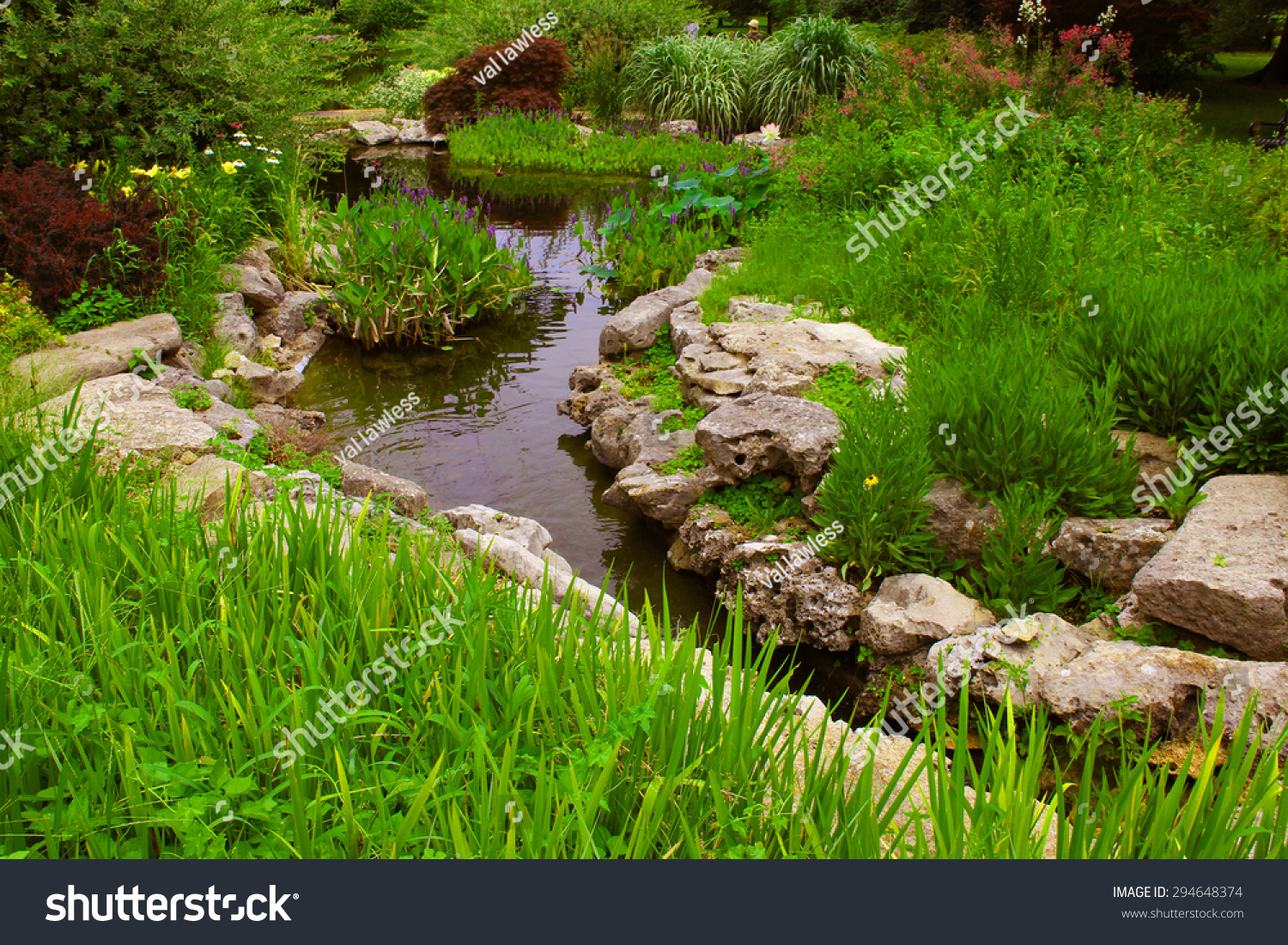 Decorative rocks near a small pond in a garden stock photo for Pond pebbles landscape rock
