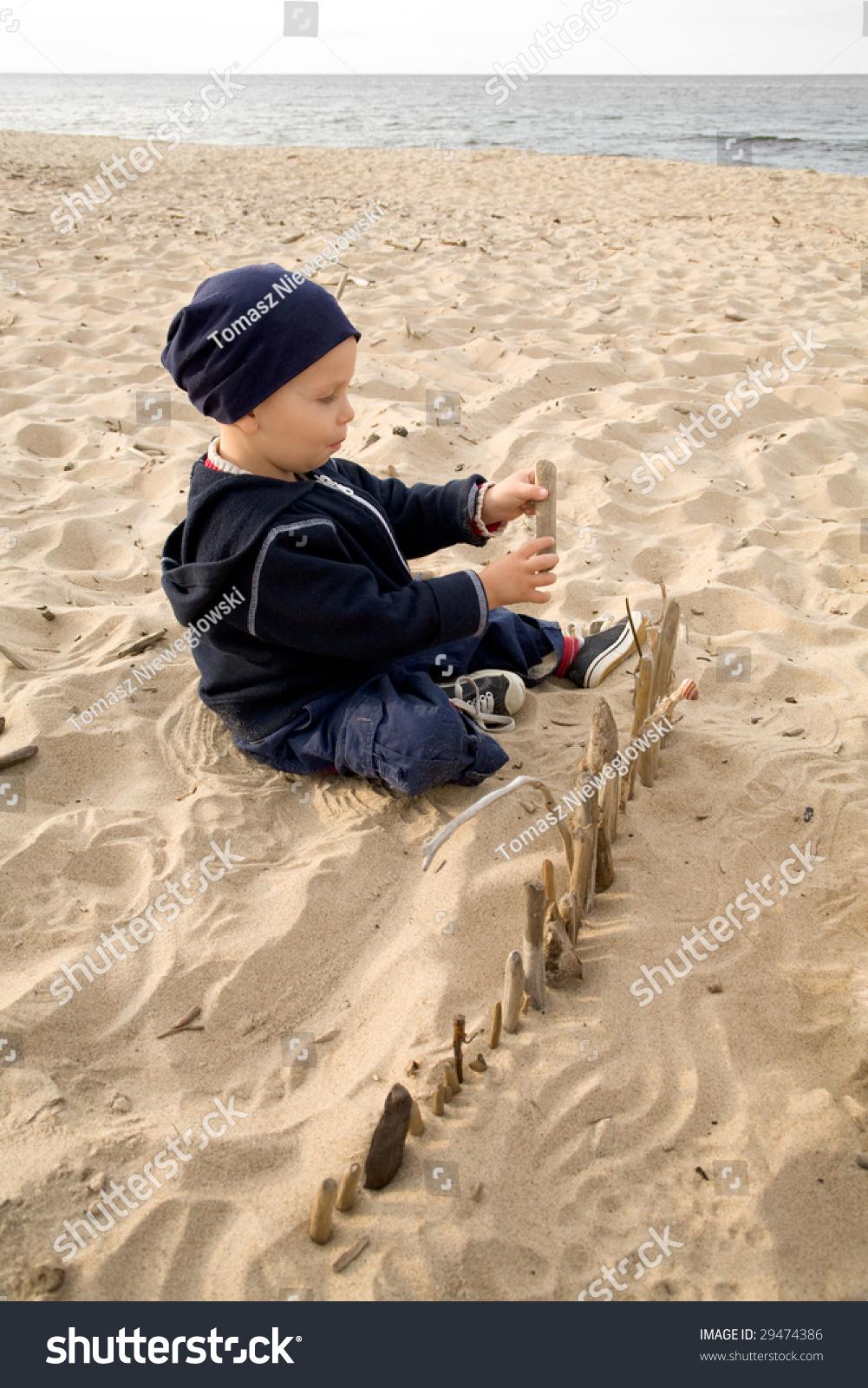boy on beach building fence sticks stock photo 29474386 shutterstock
