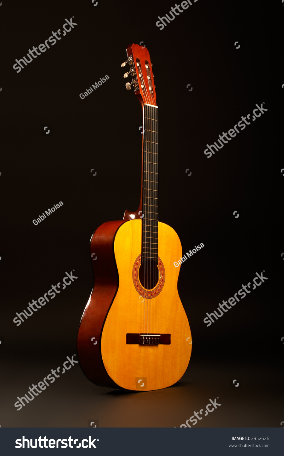 Acoustic Guitar Over Black Background Standing Stock Photo