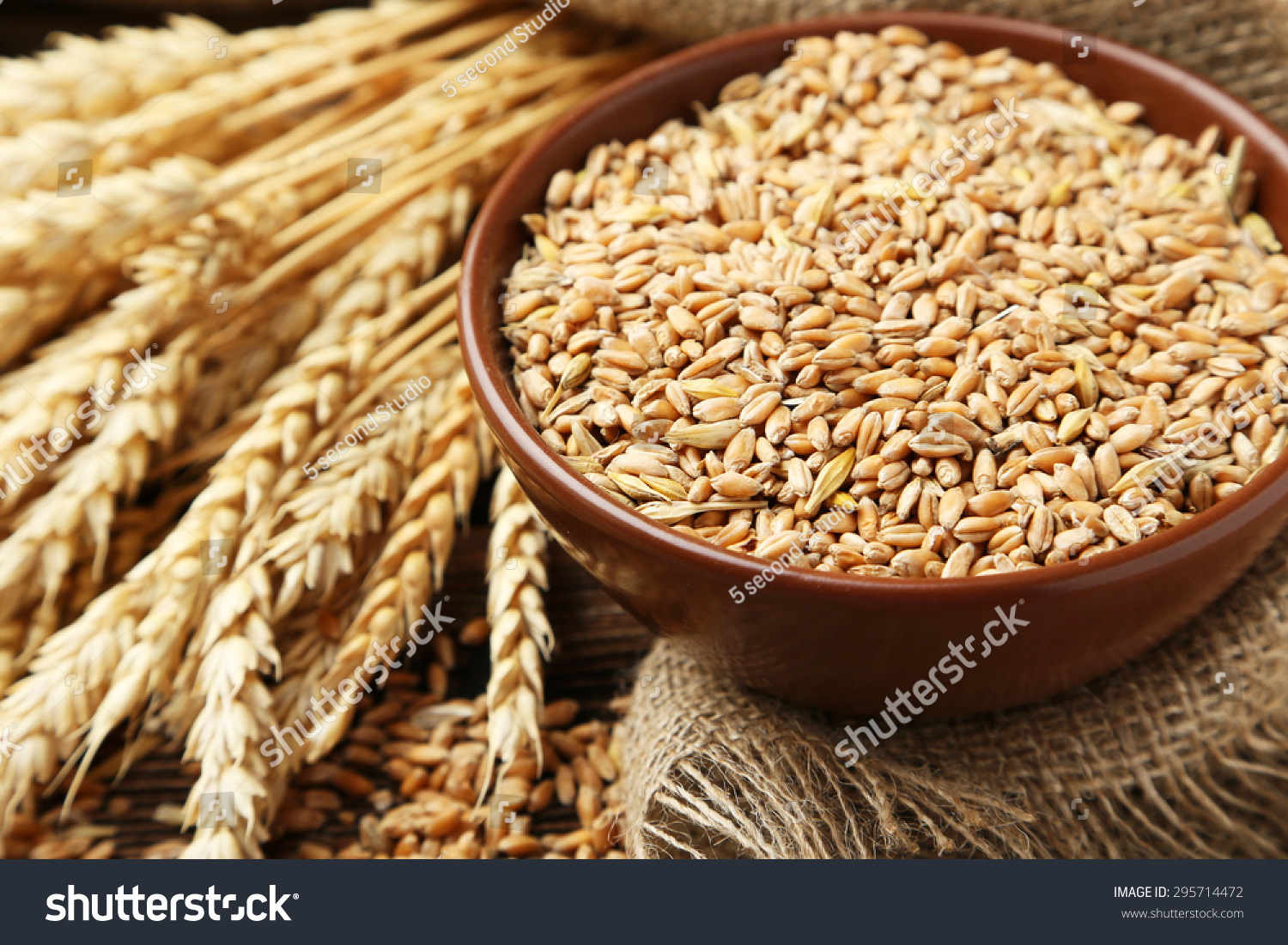 Ears of wheat and bowl of wheat grains on brown wooden background #295714472