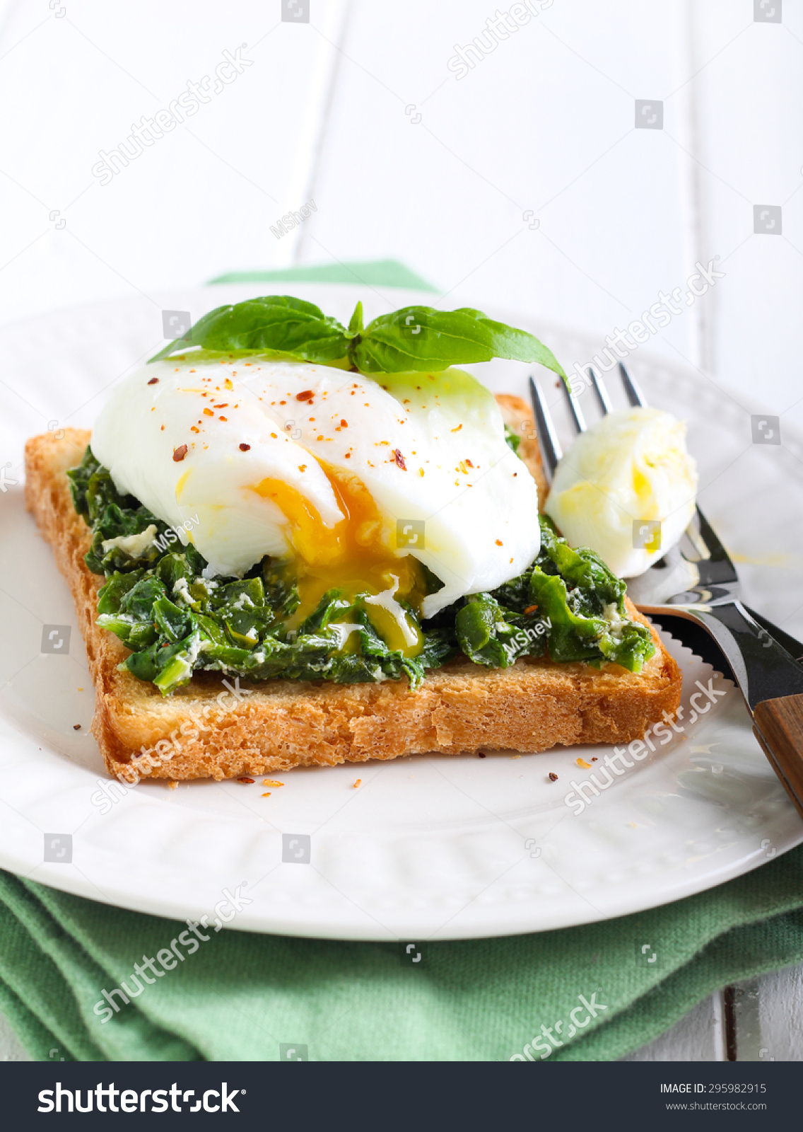 Creamy spinach and poached egg toast on plate