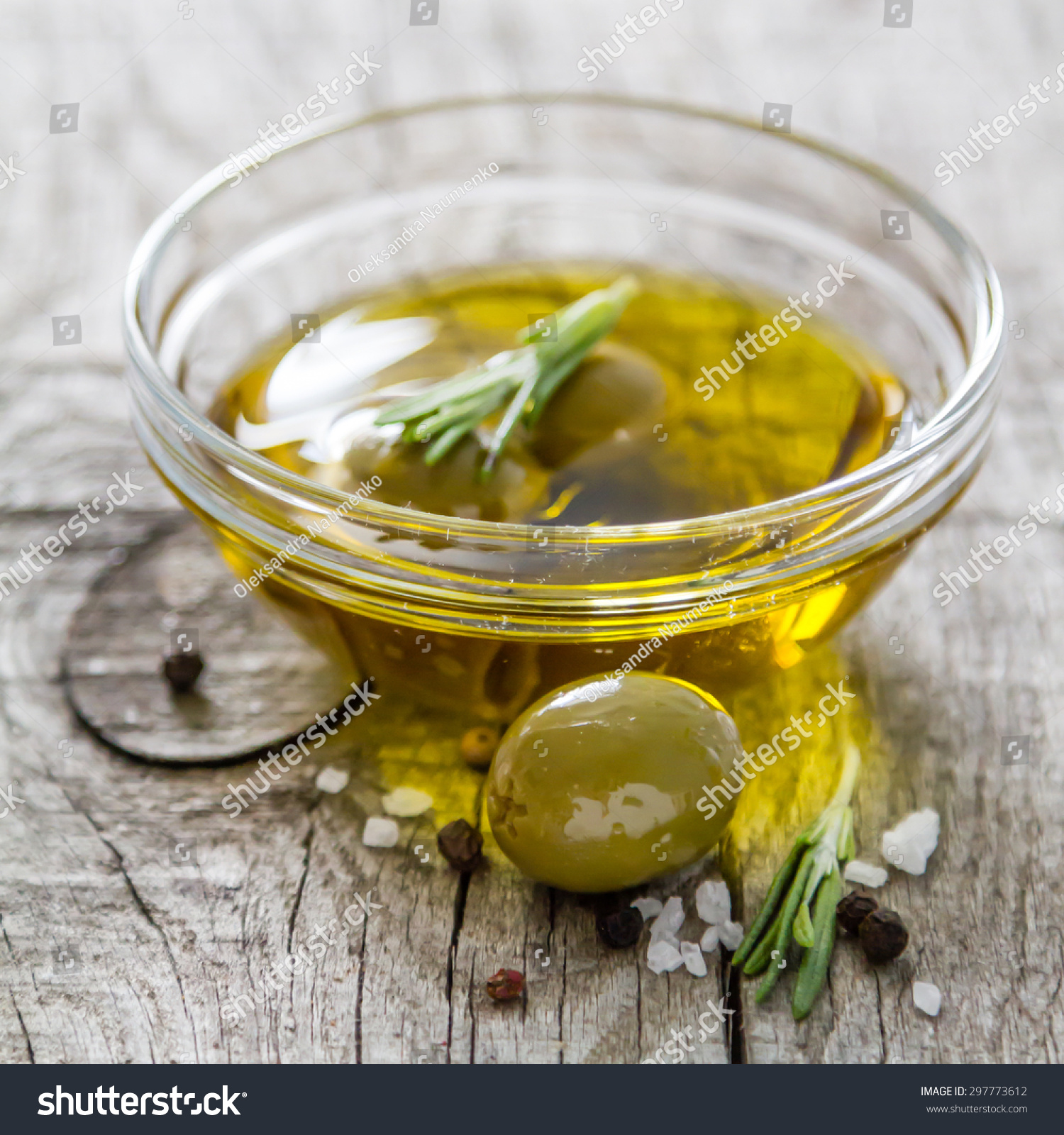 ... in glass bowl with oil, rosemary, salt, pepper, rustic wood background