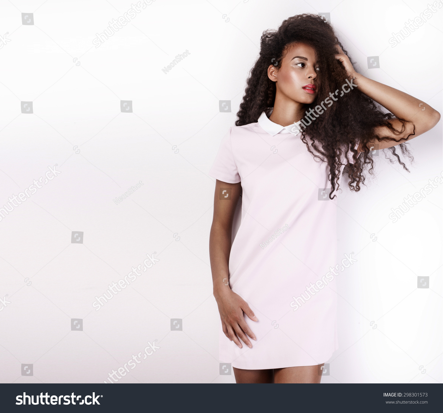 e0259c28297 Beautiful young african american woman with long healthy hair posing in  studio wearing fashionable dress.