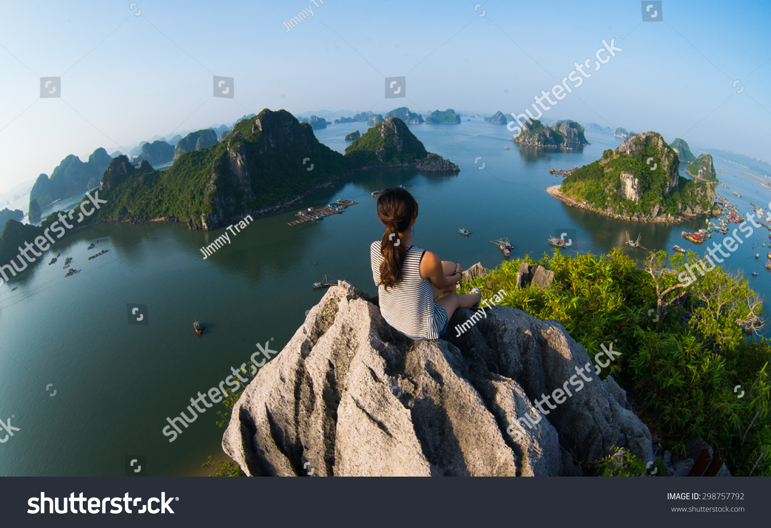 A young traveler girl sit on the top of mountain in Halong bay and enjoy the beauty of seascape. Young girl love wild life, travel, freedom. #298757792 - 123PhotoFree.com