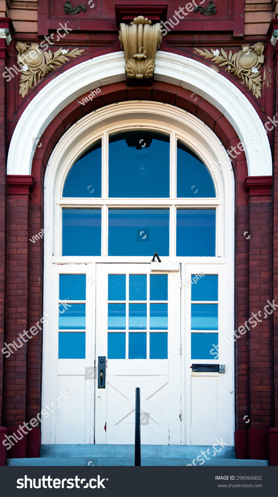 Large Arched Entrance Door With Glass Windows In A Brick Building With Stucco Embossed Exterior