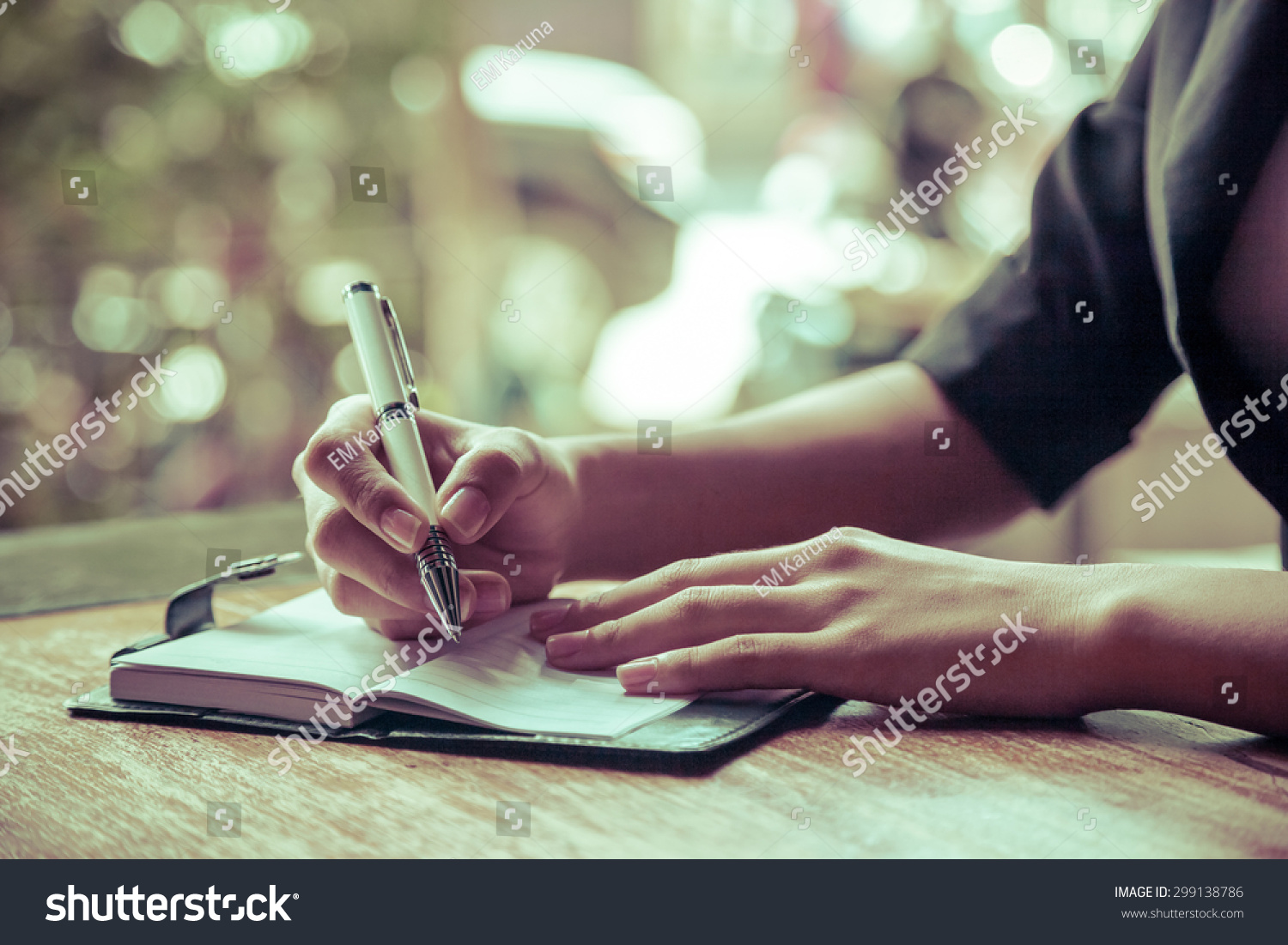 close up of woman writing her journal #299138786