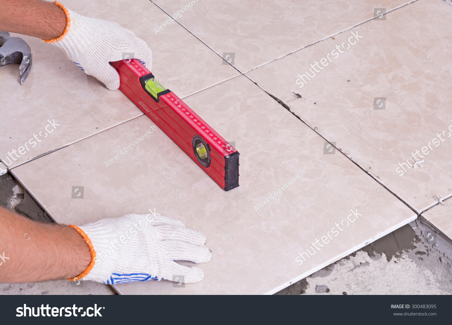 Tiler installing ceramic tiles on floor stock photo 300483095 tiler installing ceramic tiles on a floor dailygadgetfo Image collections