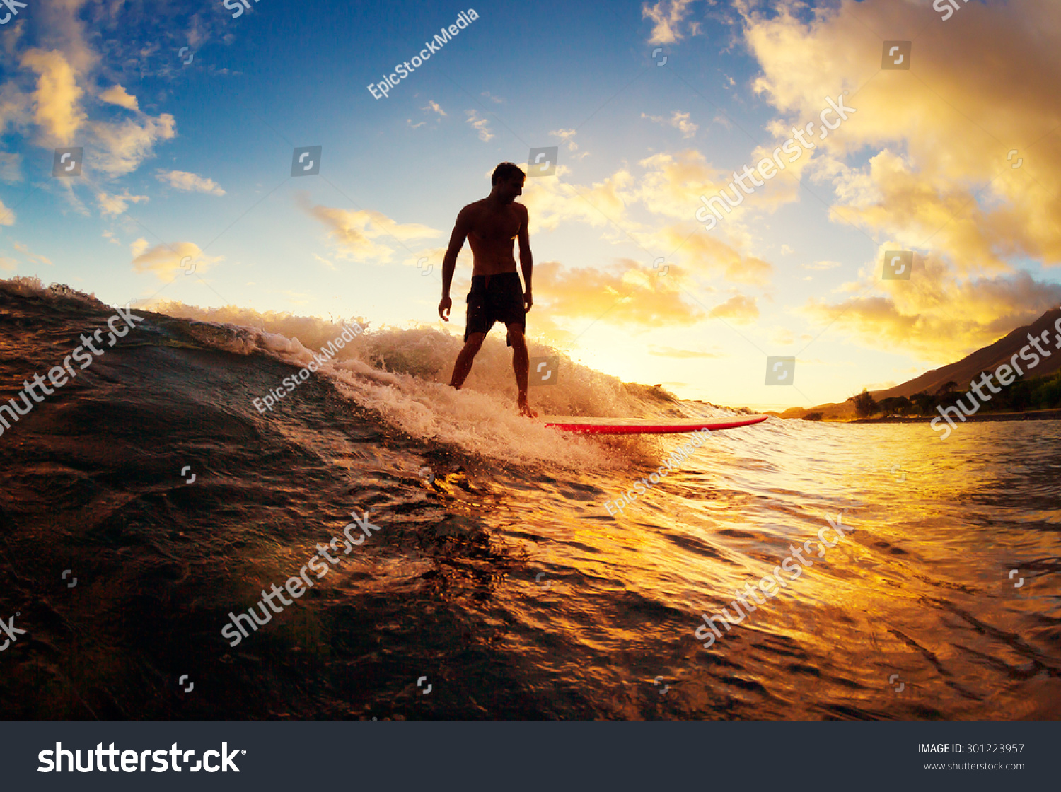 Surfing At Sunset. Young Man Riding Wave At Sunset ...