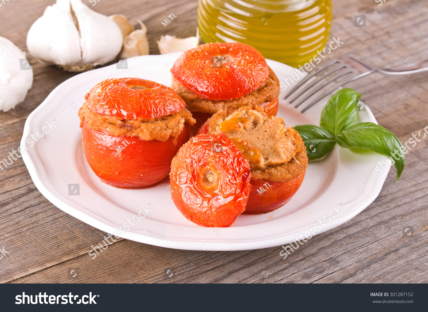 Stuffed tomatoes on glass bowl.  #301287152