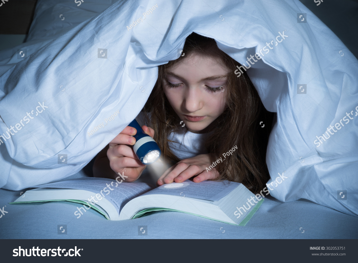 Girl reading book flashlight under blanket stock photo royalty free girl reading book with flashlight under the blanket on bed sciox Gallery