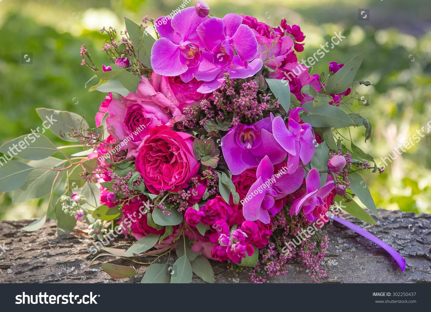 Big beautiful pink and purple wedding bouquet lying on a wooden ...