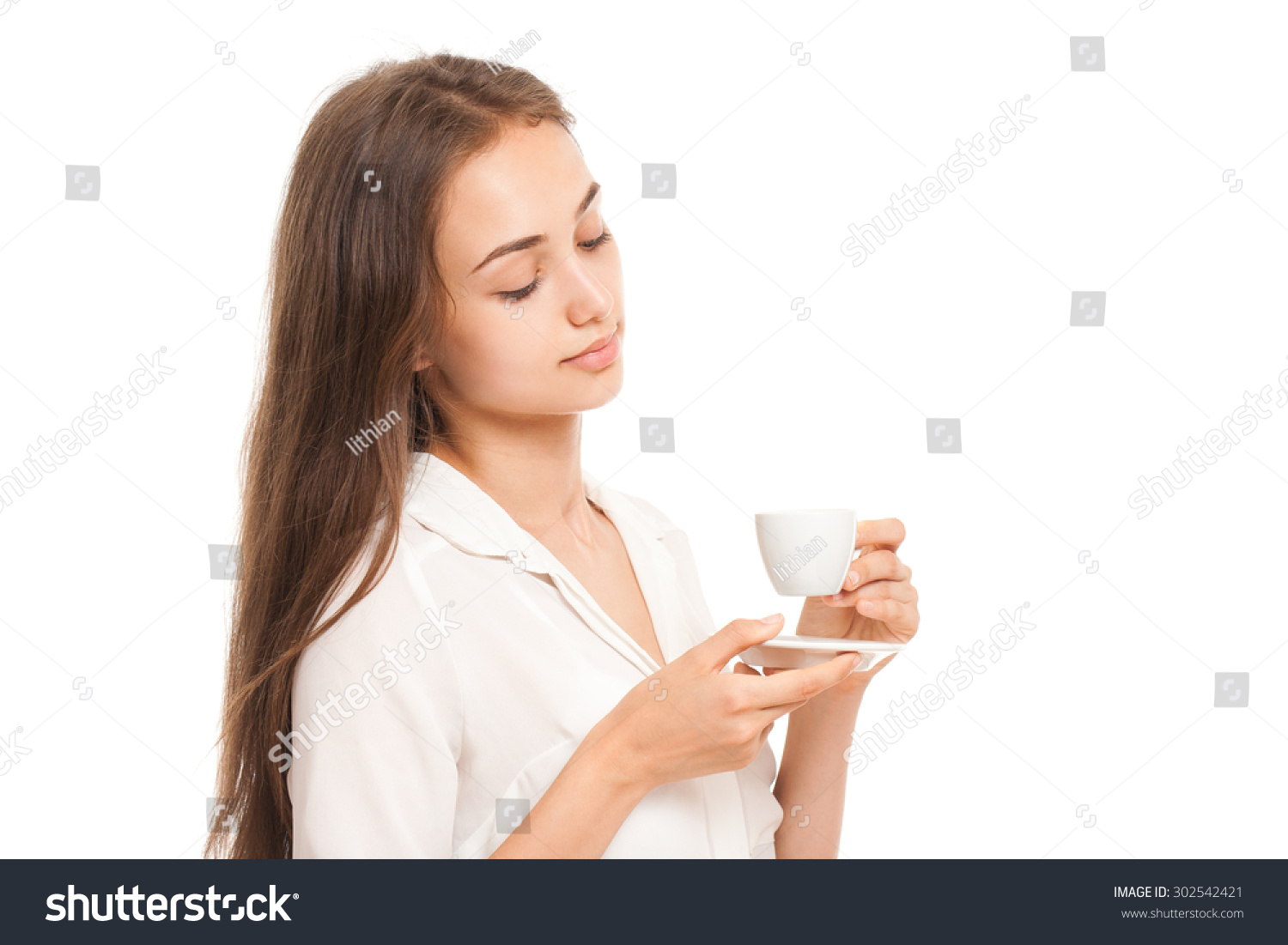 Portrait of a gorgeous young brunette woman having a cup of espresso coffee