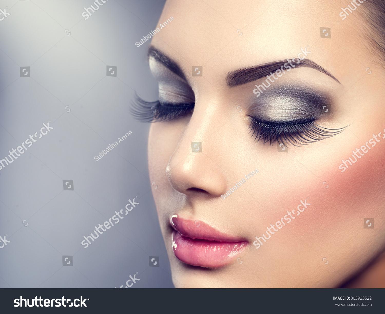 Beautiful Fashion Luxury Makeup, long eyelashes, perfect skin facial make-up. Beauty Brunette model woman holiday make up close up. Eyelash extensions, false eyelashes.  #303923522