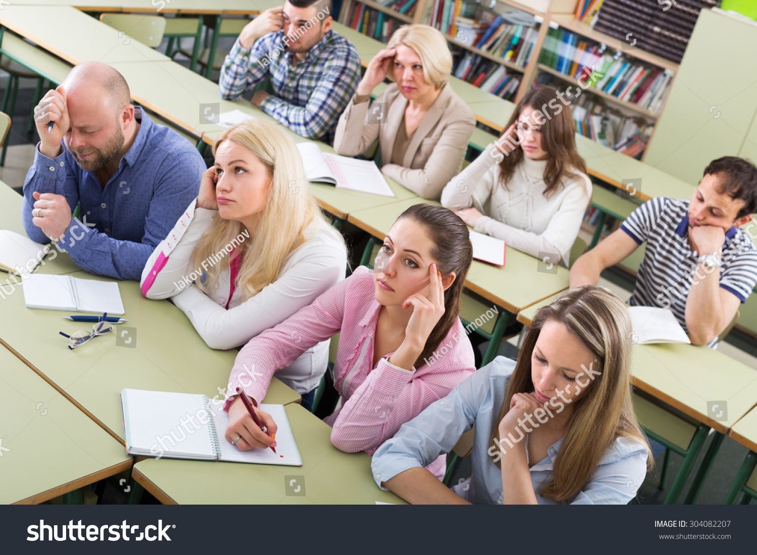 Bored Unhappy Adult Students Sitting At Lesson In ...