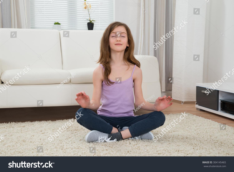 Girl sportswear doing meditation living room stock photo for Meditation living room