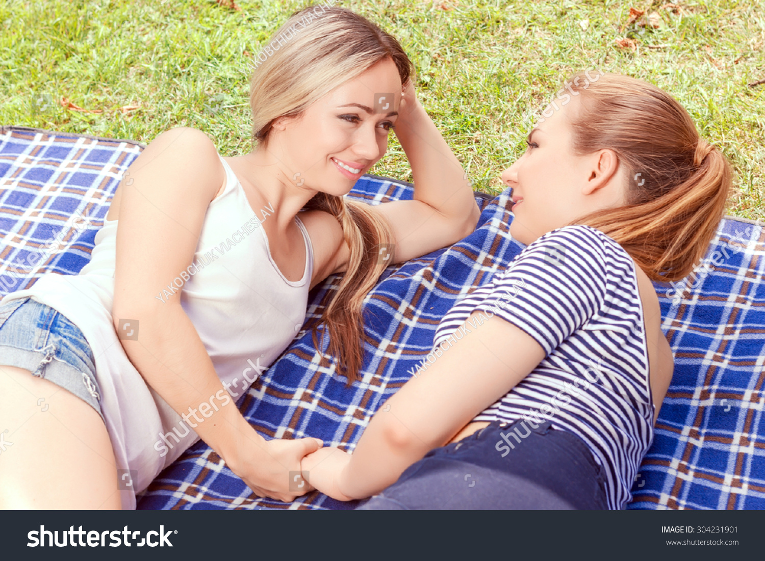 Two pretty young lesbian women lying on cover in park and looking at