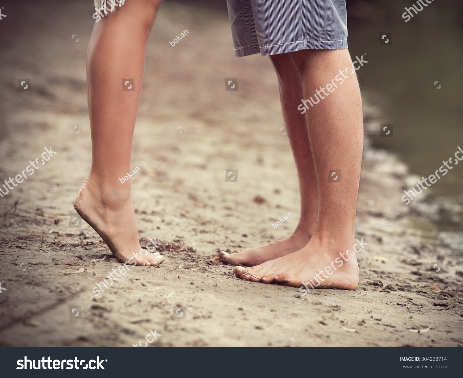 Close-up of barefoot pair of human's feet on sandy beach standing next to the lake  #304238714