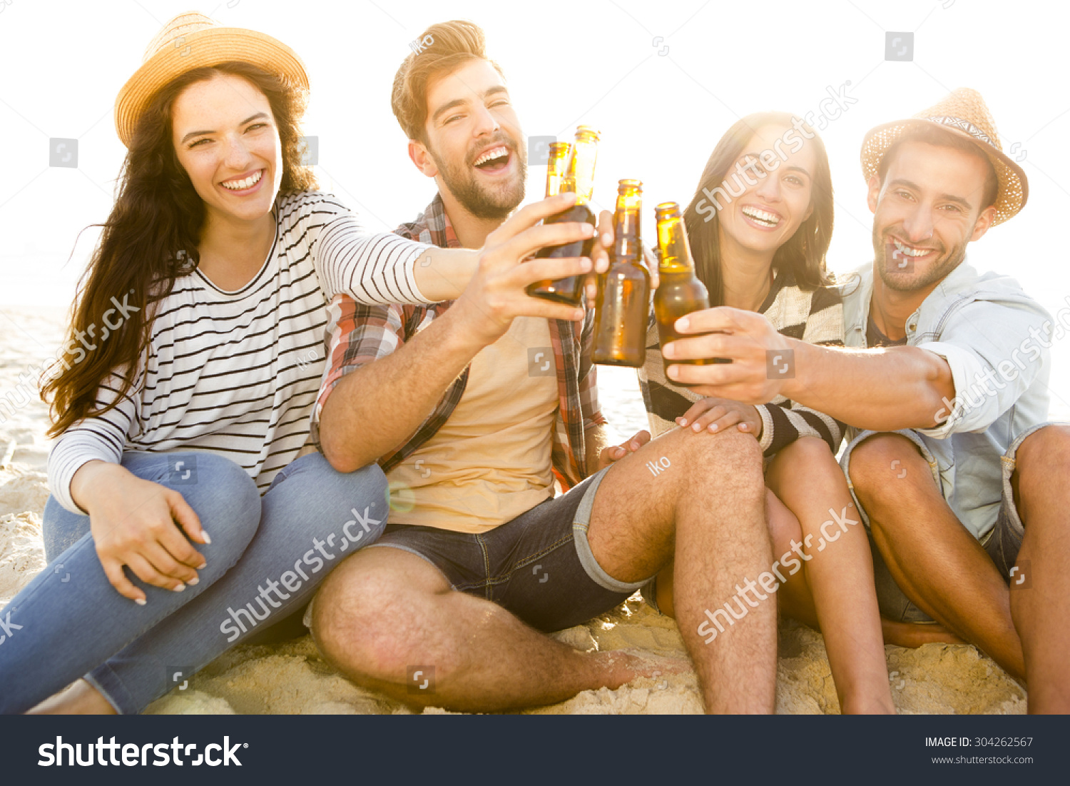 Friends having fun together at the beach and drinking a cold beer