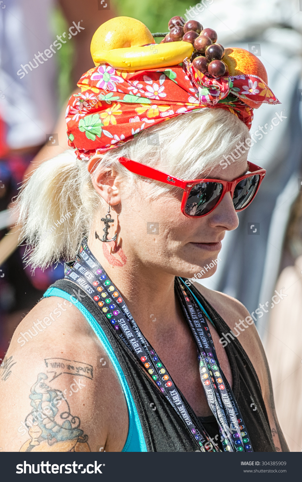 STOCKHOLM, SWEDEN - AUGUST 1, 2015: Blonde woman with fruits on head giving  away neckbands at the Pride parade in Stockholm. Approx 400.000 spectators  at ...