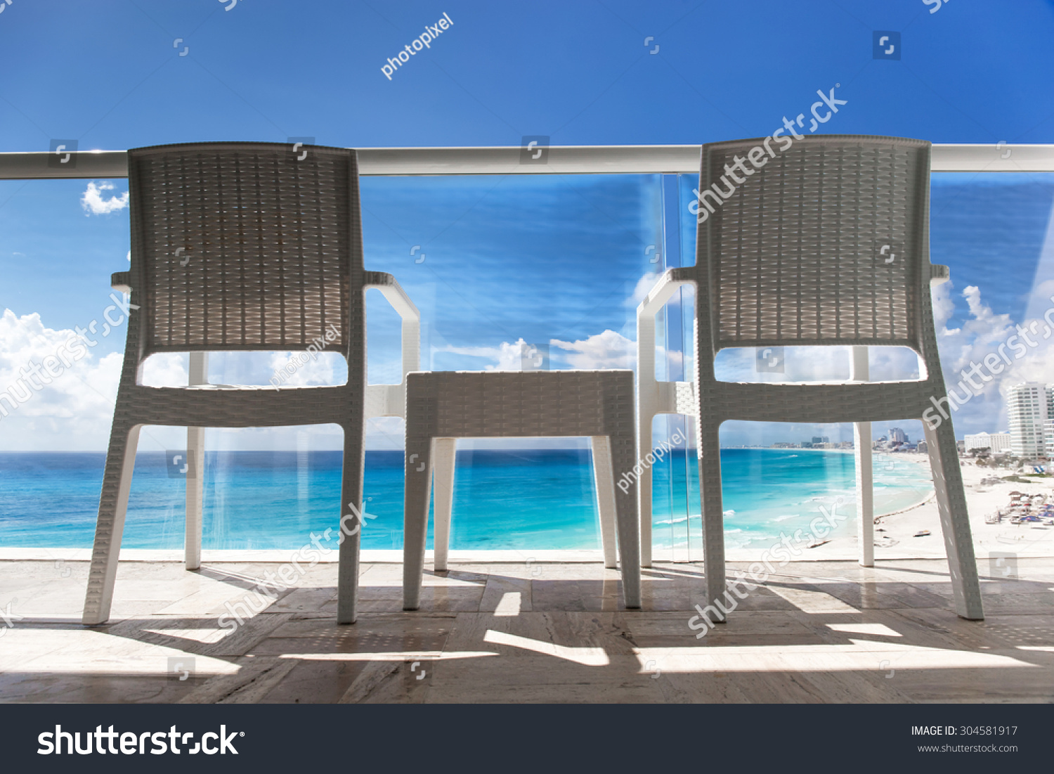 Balcony with wicker chairs and table overlooking an ocean for Balcony overlooking ocean