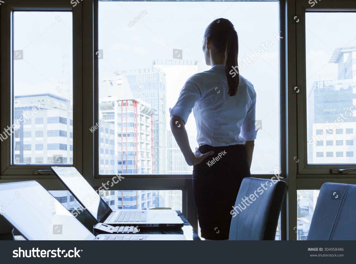 Woman He fice Looking Out Window Stock