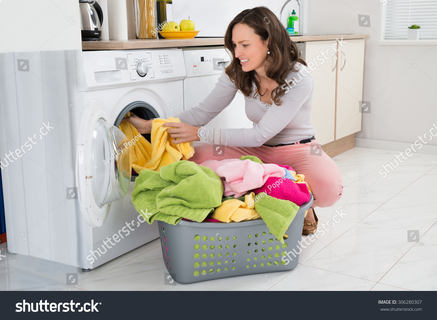 Clothes Washing Machine ~ Young woman putting clothes into washing stock photo