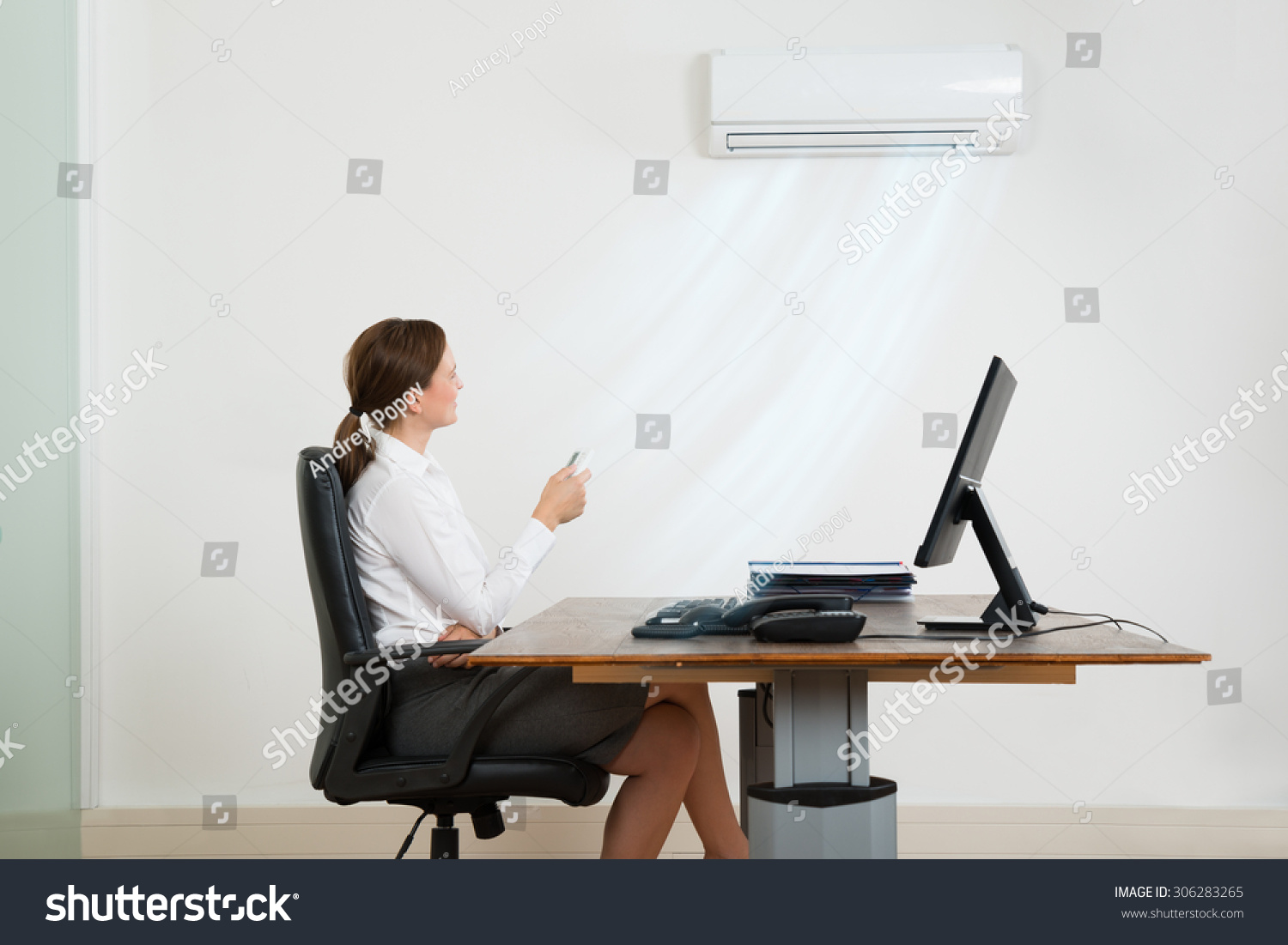 Young Businesswoman Sitting On Chair Using Air Conditioner In Office