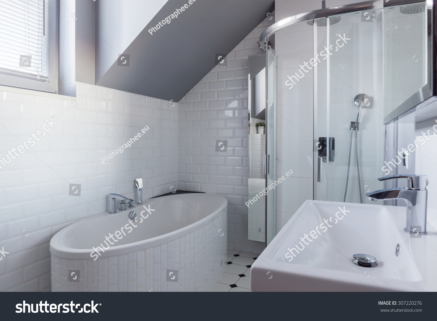 Bathroom in a luxurious apartment downtown. White and grey colors ...