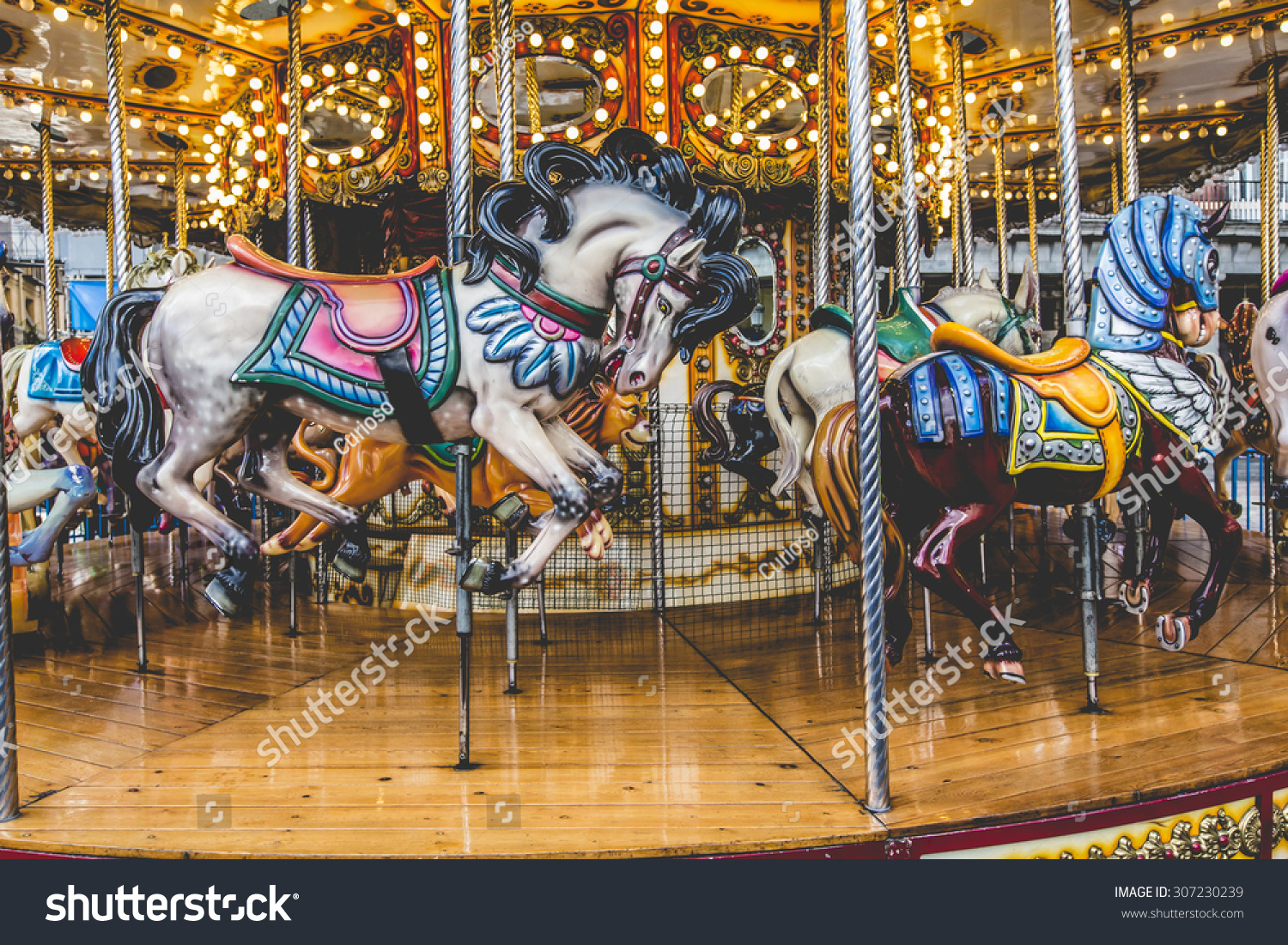 Old French Carousel In A Holiday Park. Three Horses And ...