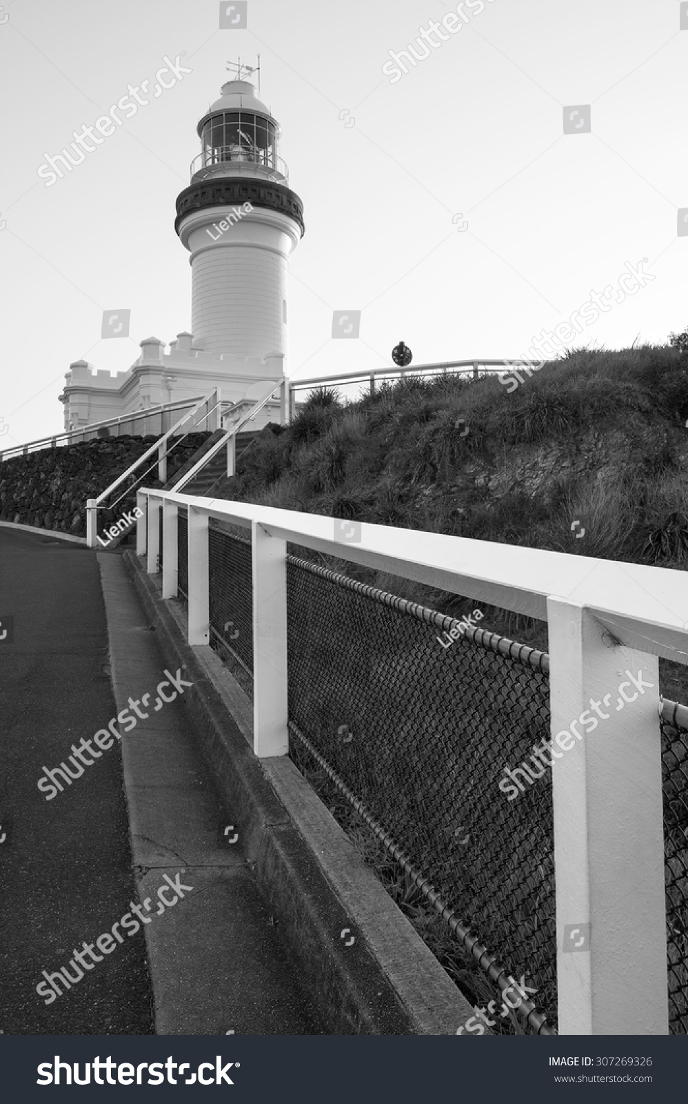 Black and white photo of the iconic cape byron lighthouse on top of a hill