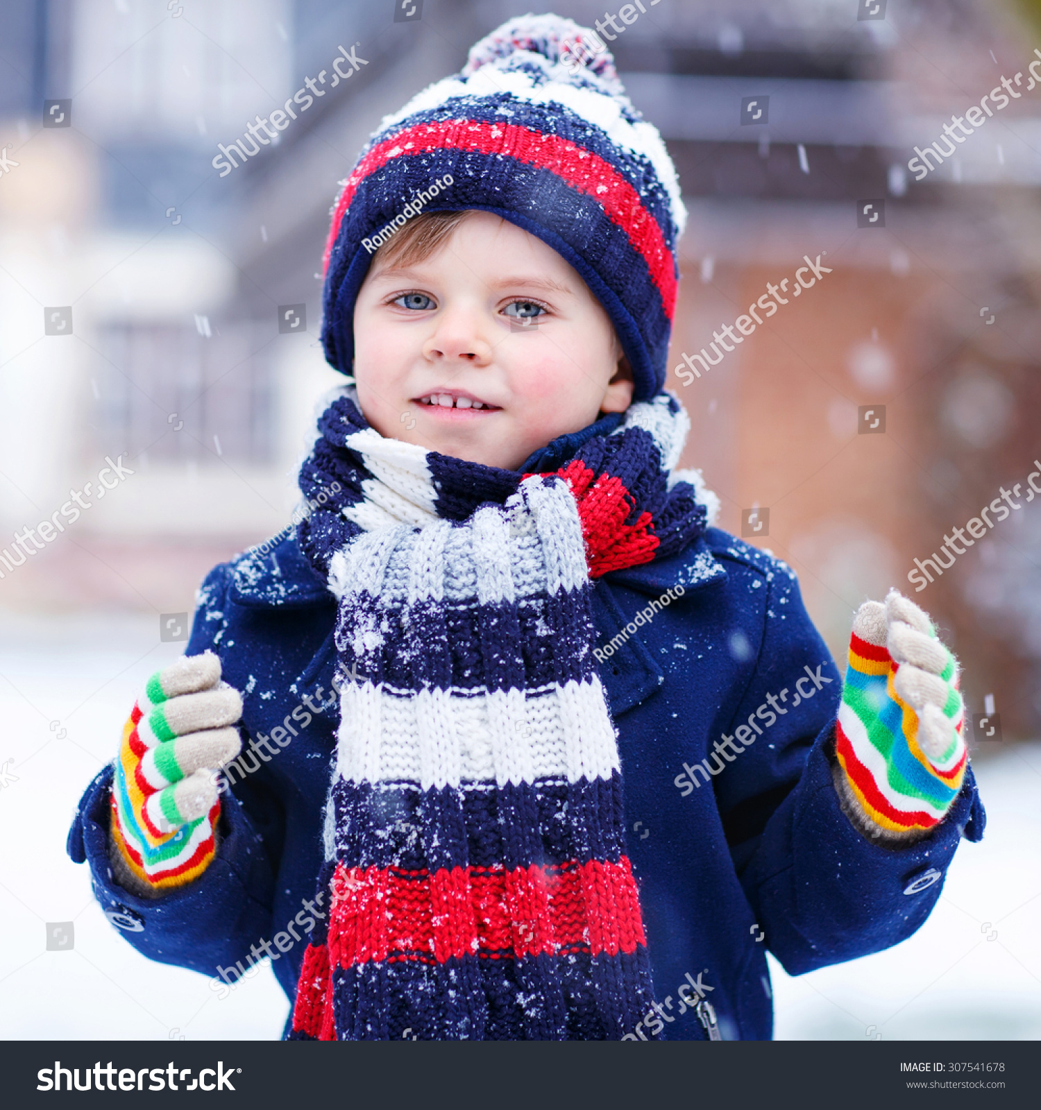 ccef1422ee7 Portrait of little funny boy in colorful winter clothes having fun with snow