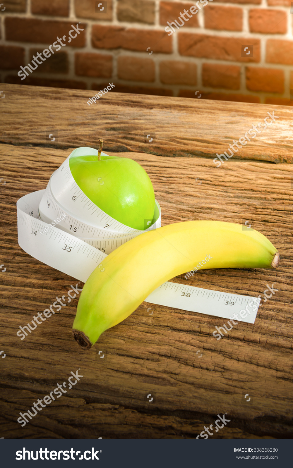 Measuring tape wrapped around green apple stock photo 308368280 measuring tape wrapped around a green apple and banana on wooden table as a symbol of biocorpaavc