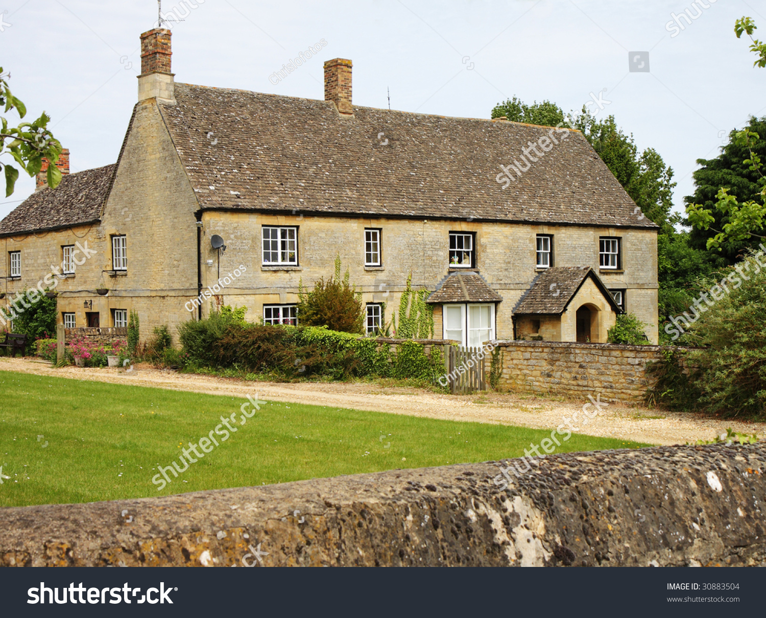 Traditional Cotswold Stone English Rural Farmhouse With Wall To The Front