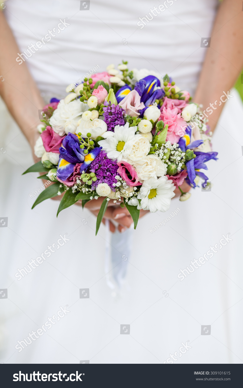The Bride Holds A Wedding Bouquet Of Colorful Flowers And White