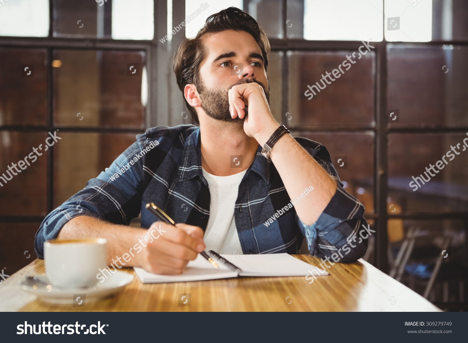 Young man taking notes in his notebook at a cafe #309279749